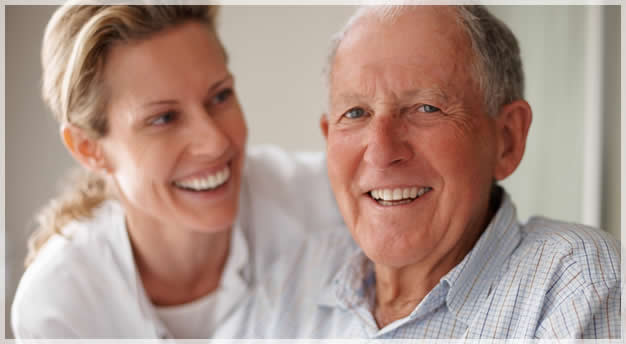 elderly man and caregicer smiling